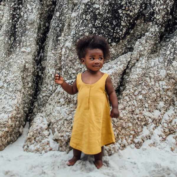african girl on beach wearing mustard tank dress gray label by KiND