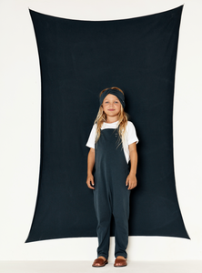 Girls wearing white shirt and twisted headband and blue salopette dungaree in 100% organic cotton jersey elasticated waistband on the back with 1 button to fasten the shoulder straps