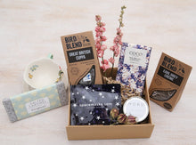 Care package items in gift box including Spacemask, Hobo soy candle, Coco Chocolatier Earl Grey Chocolate, Bird & Blend Earl Grey Creme Teabags
