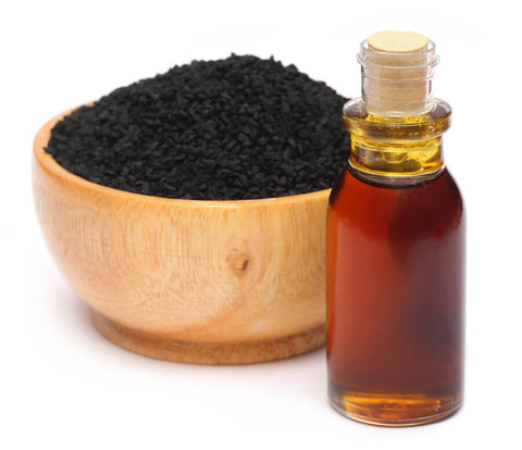 a bottle of black seed oil and a bowl of black seeds