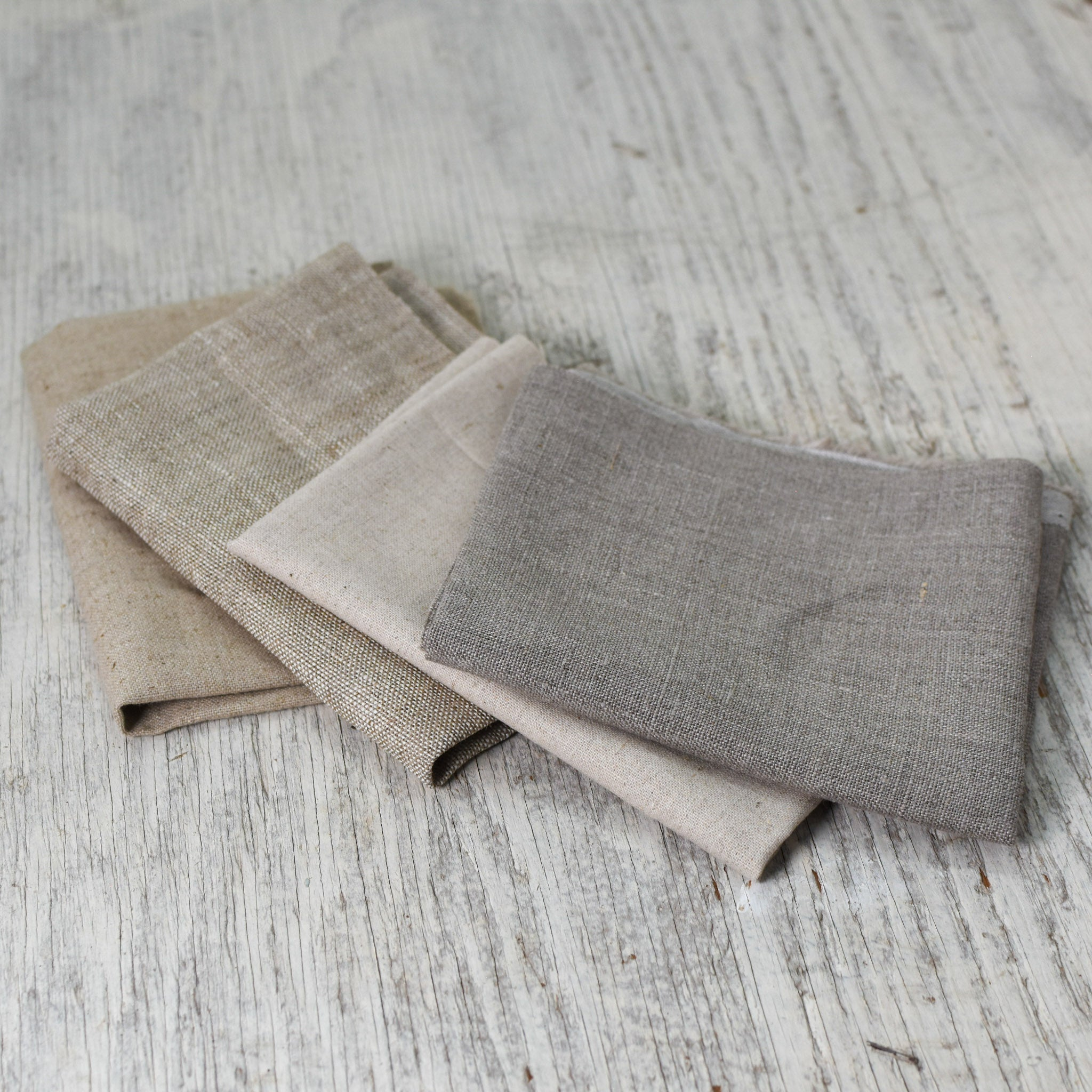 four pieces of folded natural brown linen fabric laid out in a fan shape to show variations in the colors and textures of each.