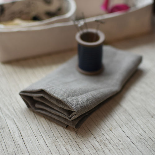 a piece of natural brown linen fabric, folded, with a blue-glazed ceramic spool pin holder in the background.