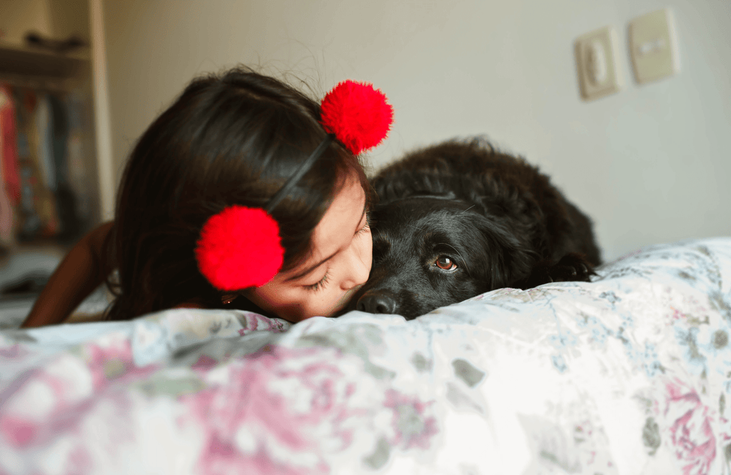 Girl sleeping next to dog in bed