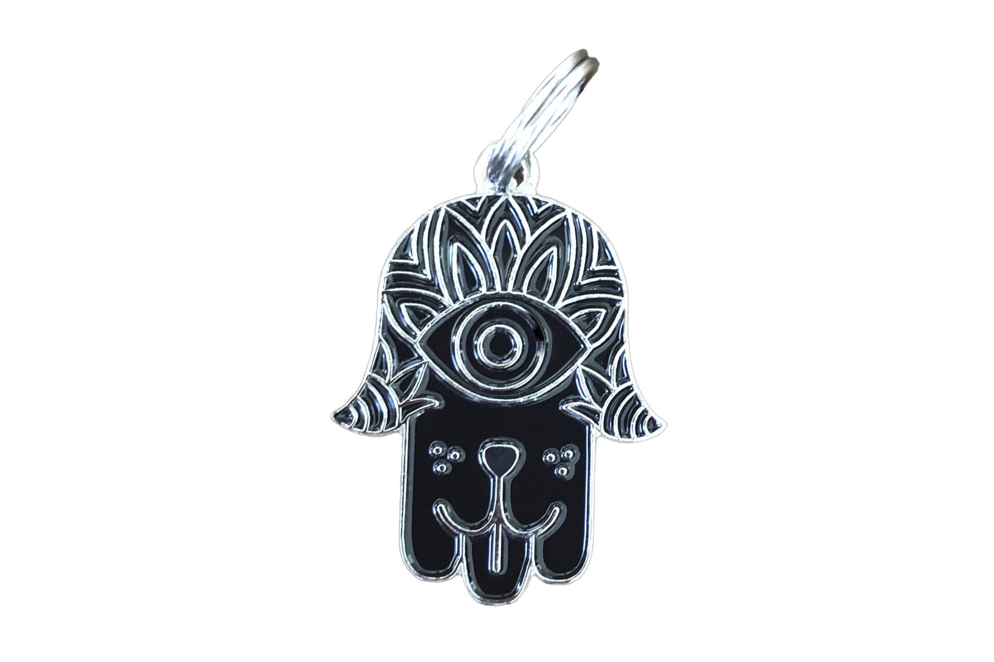 Pet ID tag made of silver plated brass and black enamel designs like a hamsa with a dog face on it sticking out its tongue.