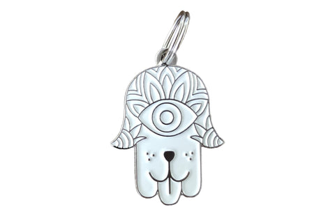 Pet ID tag made of silver plated brass and white enamel designs like a hamsa with a dog face on it sticking out its tongue.