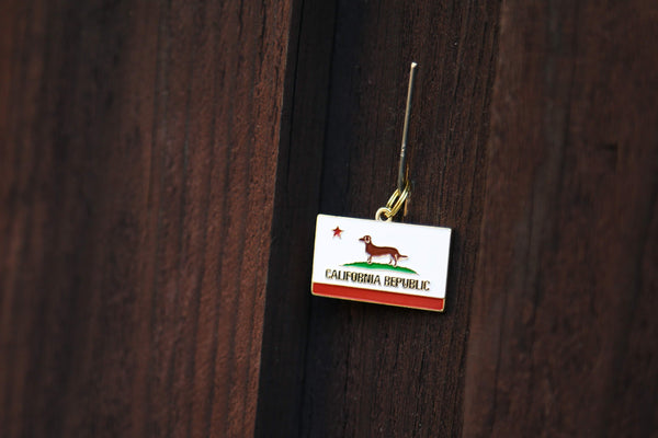Pet ID tag hanging on a nail on a brown fence. The tag is made of gold plated brass with red and white enamel in the style of a California state flag but with a small dog instead of a bear.