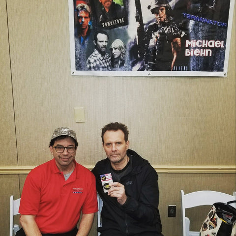 Michael Biehn of Aliens & Terminator with HonorOne founder Lane Ostrow at the 2018 Mad Monster Party holding the HonorOne Reminder Coin