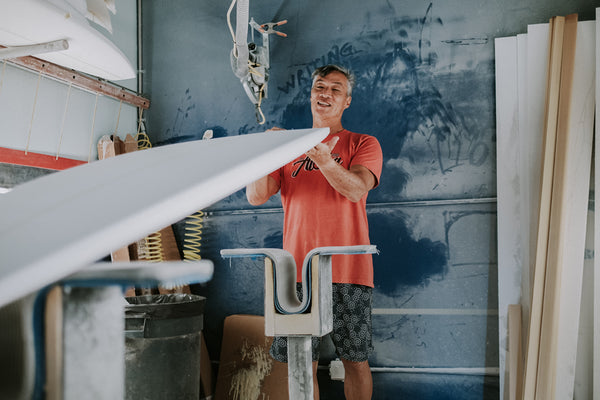 Surfboard shaper Glenn Pang inspecting his craft in shaping bay