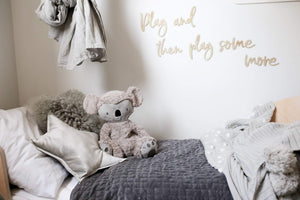 weighted toy for sensory behaviour, kevin the calming koala, resting on a bed
