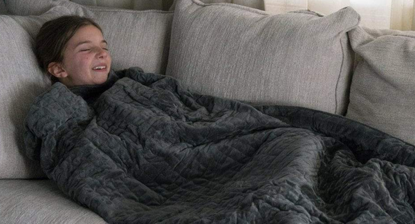 girl covered with a weighted blanket