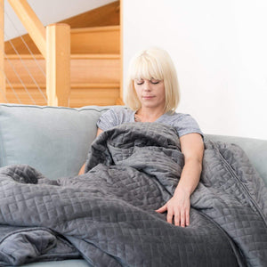 Woman sitting on a couch, covered with our granite-coloured weighted blanket. Her hand is resting on the soft blanket fabric.