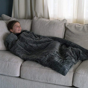 kid trying to sleep using a grey blanket on a couch