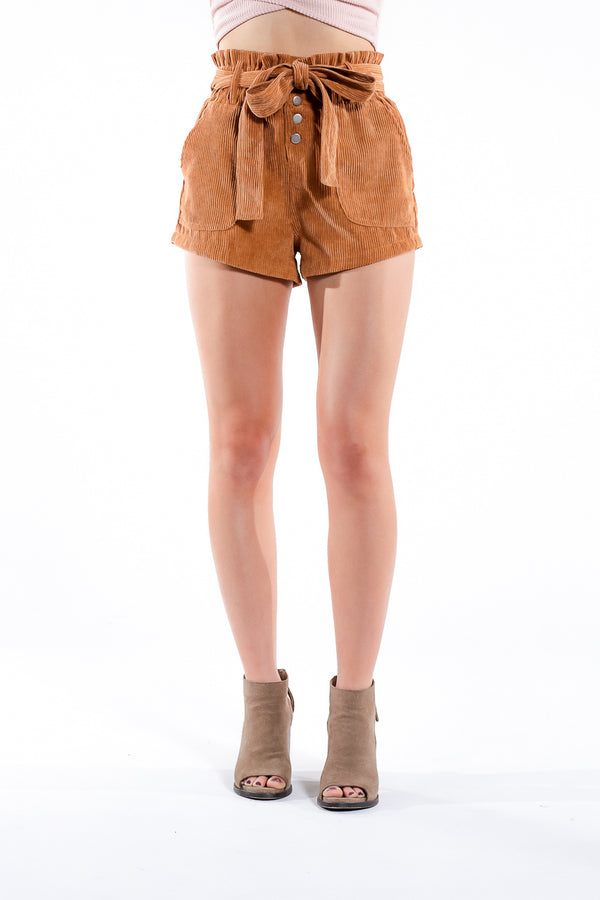 High-waisted camel-colored shorts with buttons and bowtie