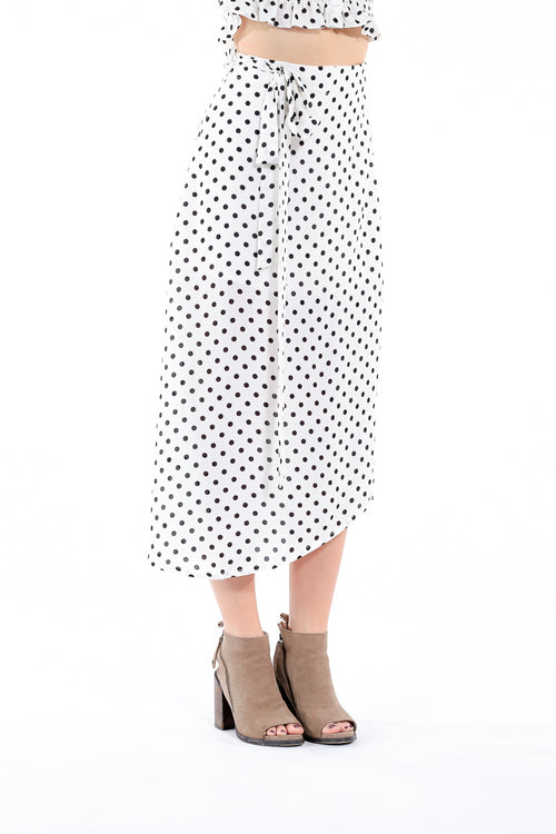 Black and white polka dot high-waisted skirt that wraps around and ties at the side