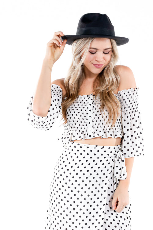 Black and white polka dot off-the-shoulder cropped top with buttons and ruffled edges