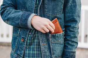 Pulling Flux veg tan leather wallet in tan out of pocket
