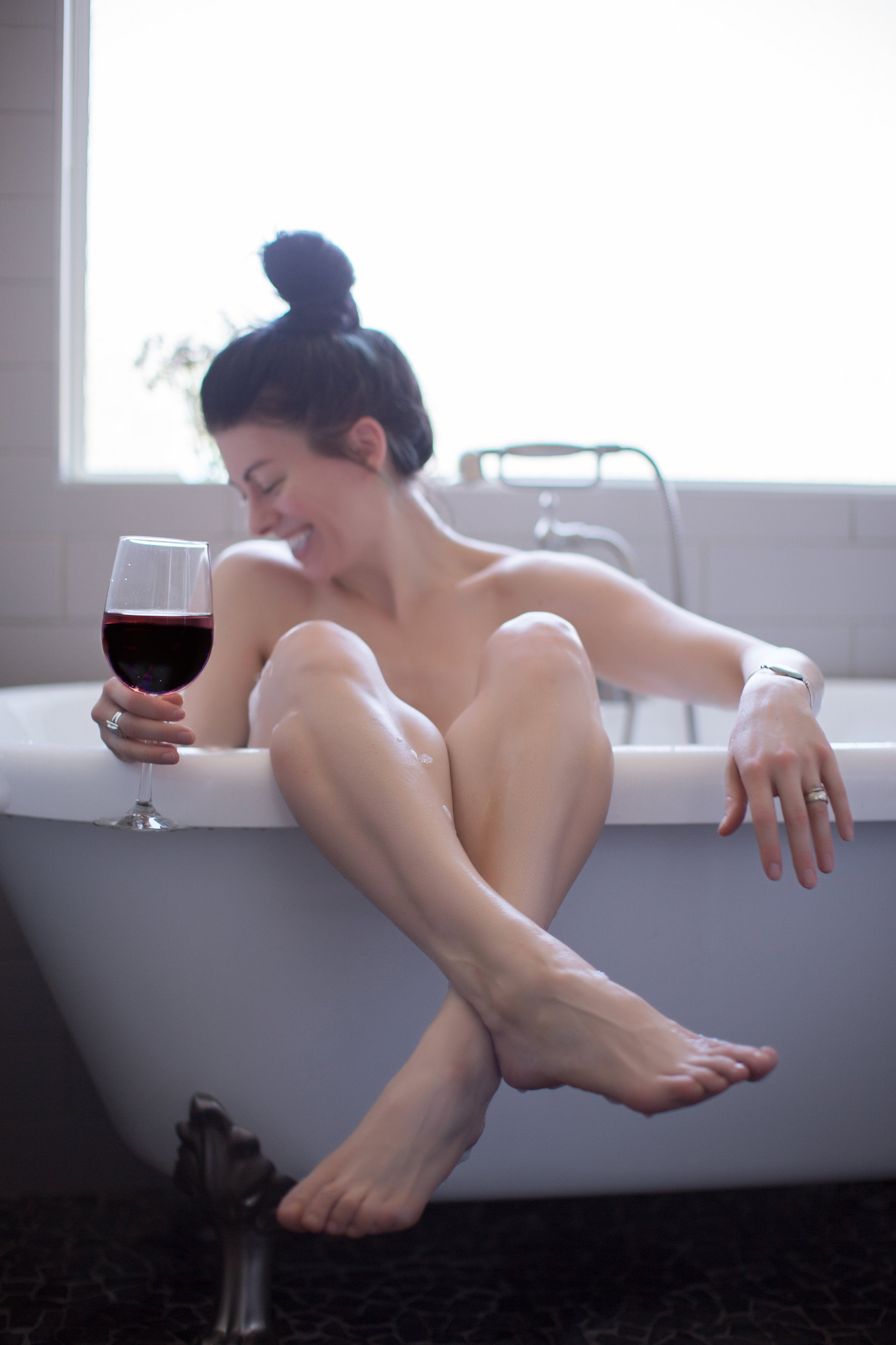 Enjoying a glass of TEMPT red blend wine in the bathtub