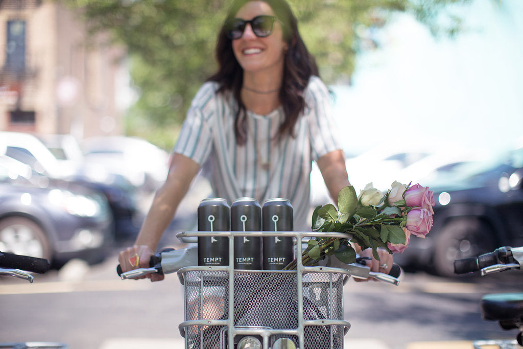 A woman taking TEMPT wine in her bicycle basket