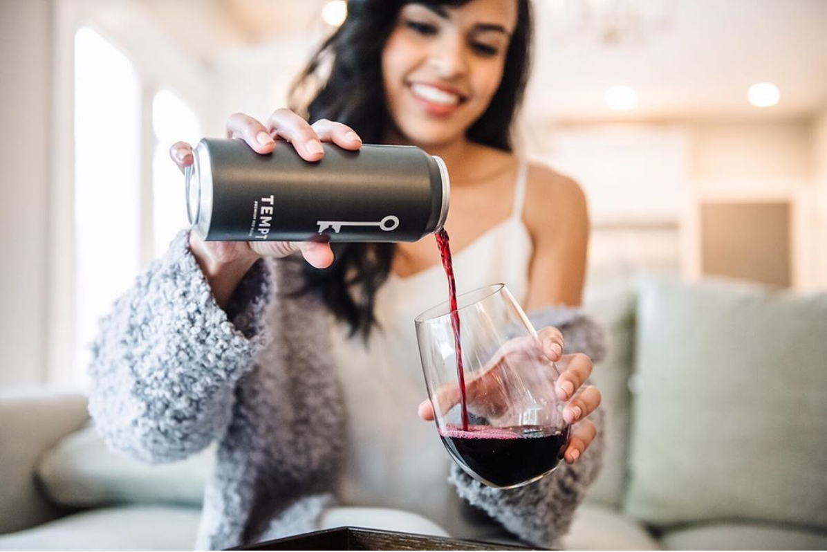 Woman pouring a glass of TEMPT red blend wine in a cozy sweater