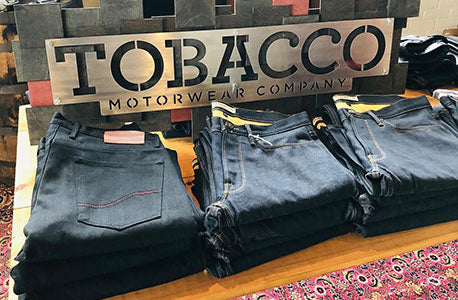 Tobacco jeans on display table in Clutch & Throttle.