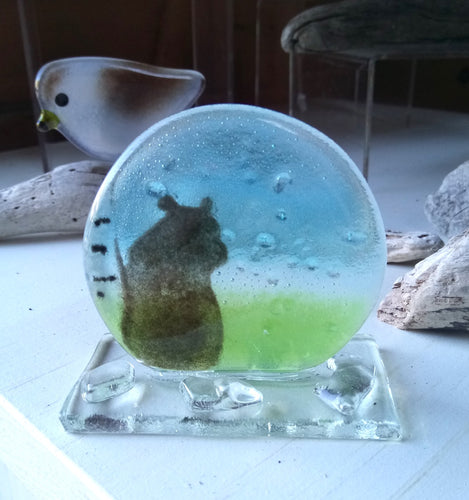 Dome shaped glass featuring a Brown bear leaning against a birch tree.