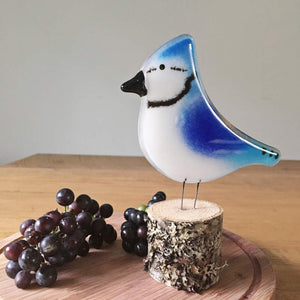 Blue Jay Glass Ornament placed on wooden chopping board with  grapes