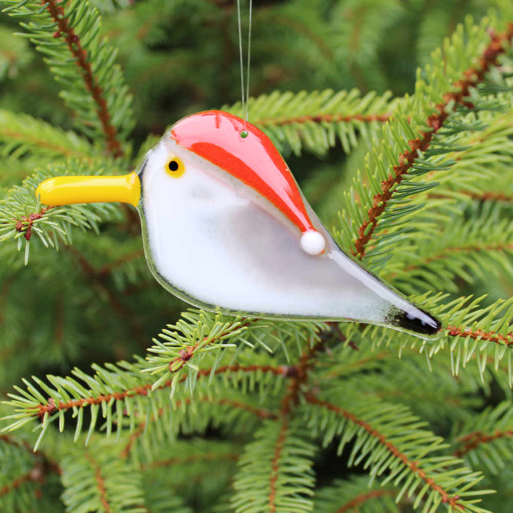 A close up photo of a glass seagull in a red Santa Hat hangs from a Pine Tree. This is a Christmas Tree Decoration.