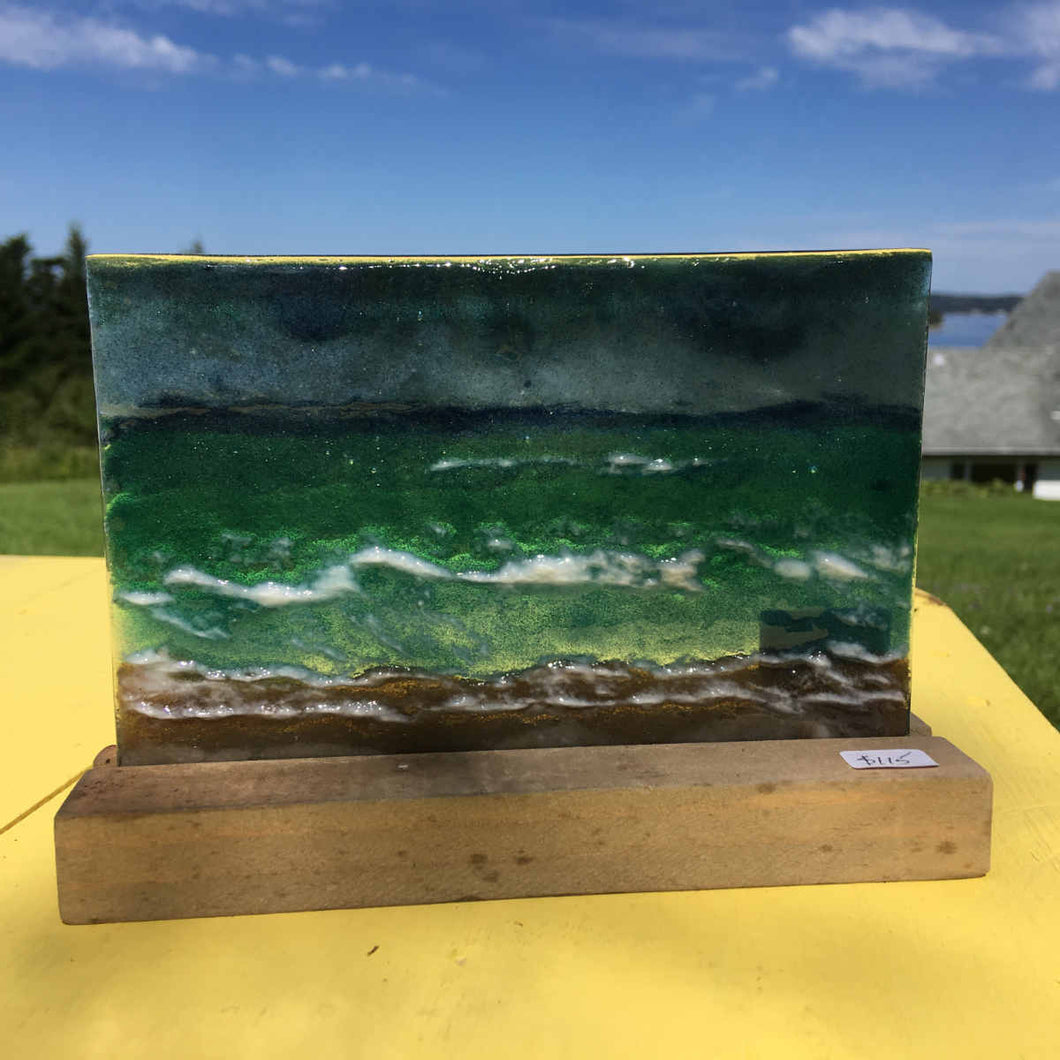 A glass picture tile in a pine slotted stand. The glass depicts a coastal scene with choppy seas, wet sand and moody skies.
