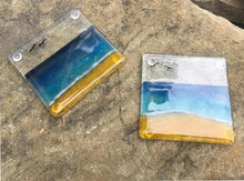 Load image into Gallery viewer, Two glass coasters featuring a blue, aqua and sandy coloured beach scene.