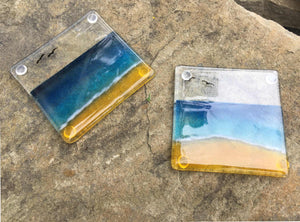 Two glass coasters featuring a blue, aqua and sandy coloured beach scene.
