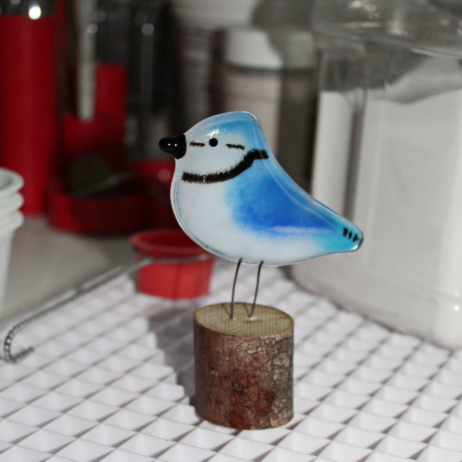 A blue and white glass blue jay bird perches on a log.