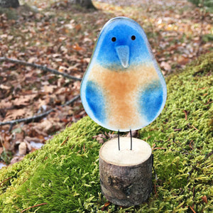 bluebird chick - blue and peachy orange coloured glass bird on log perch. The background is a mossy rock and autumn leaves.