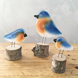 Three different sized blue, tan and white glass birds modelled on the Eastern Bluebird