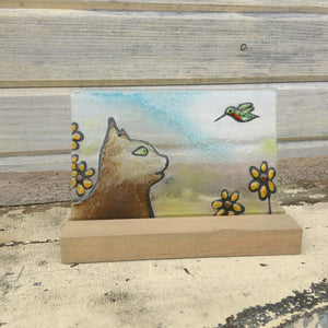 Brown siamese looking cat watching a hummingbird in amongst the yellow brown eyed susan flowers. Glass tile.