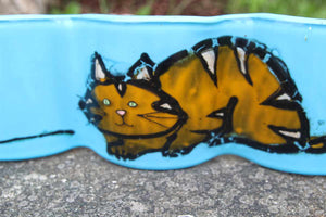 Close up of glass art featuring a ginger and gold cat