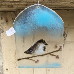 Arched shaped glass suncatcher featuring chickadee in a branch with purple berries.