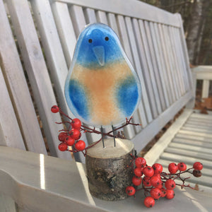 A blue and tan glass bluebird ornament is perched on a grey-washed garden bench with rowan berries around his feet.
