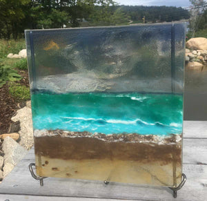 A steel grey, teal and brown glass picture panel beach scene