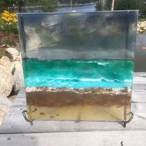 A handcrafted beachscape glass panel in an iron stand