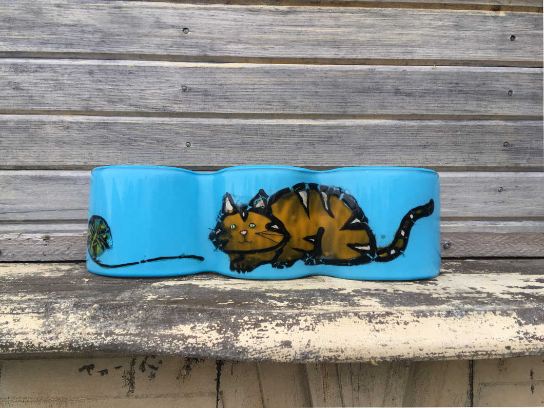 Aqua wave of glass with orange and gold coloured tabby cat
