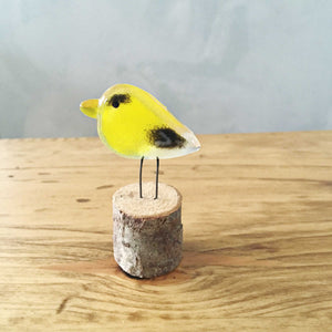 A pocket sized goldfinch made of yellow and black glass