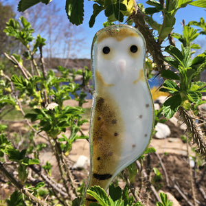 A brown and white glass Barn owl hangs in a thorny rose bush