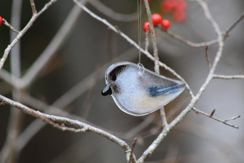 Cute hanging glass Chickadee with branches and red berries in the background