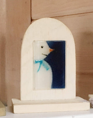 Table Top Ornament: Glass picture tile featuring snowman in blue scarf, mounted on a wooden white arch