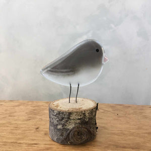A grey and white glass bird ornament with a pink beak (Dark Eyed Junco).