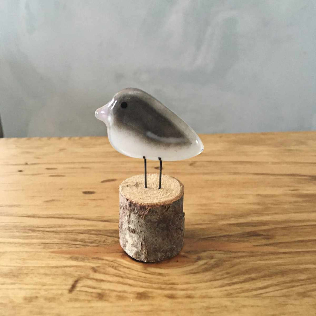 A small grey and white glass bird ornament with a pink beak. (Dark Eyed Junco)