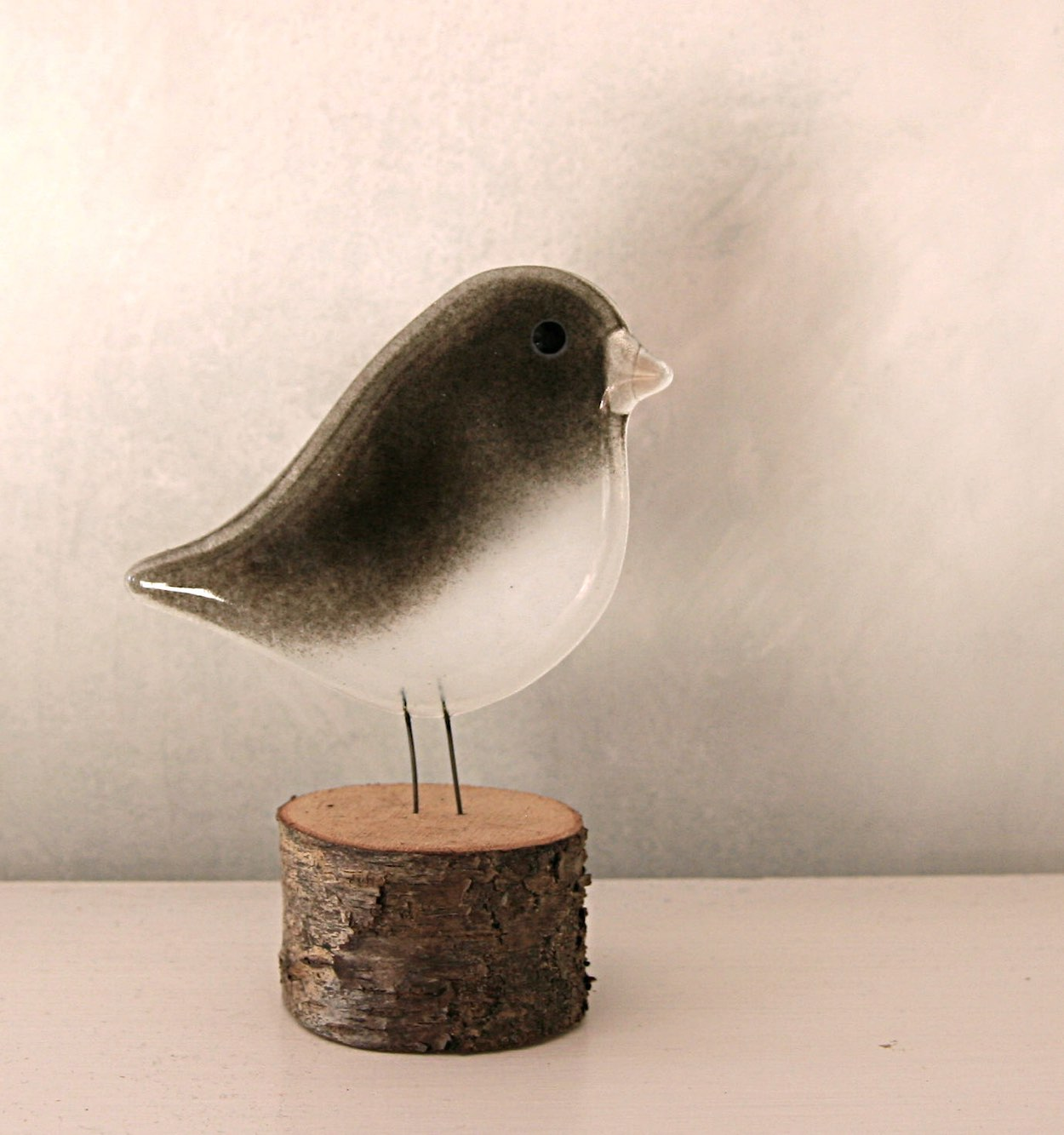 Junco Bird Ornament on a log perch. The bird is made by The Glass Bakery