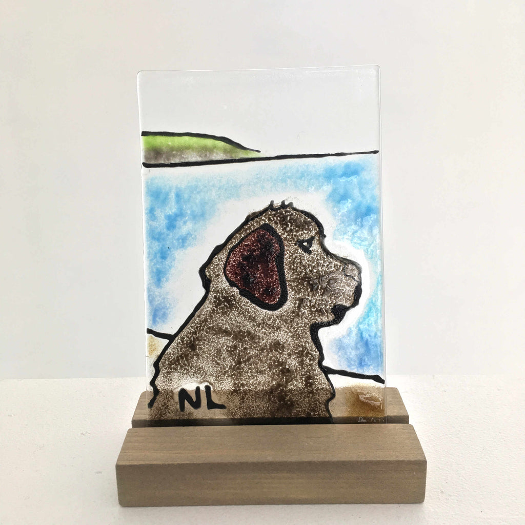 A studio-glass tile featuring a side profile of a Newfoundland dog gazing out to sea. The glass tile is in a wood stand.