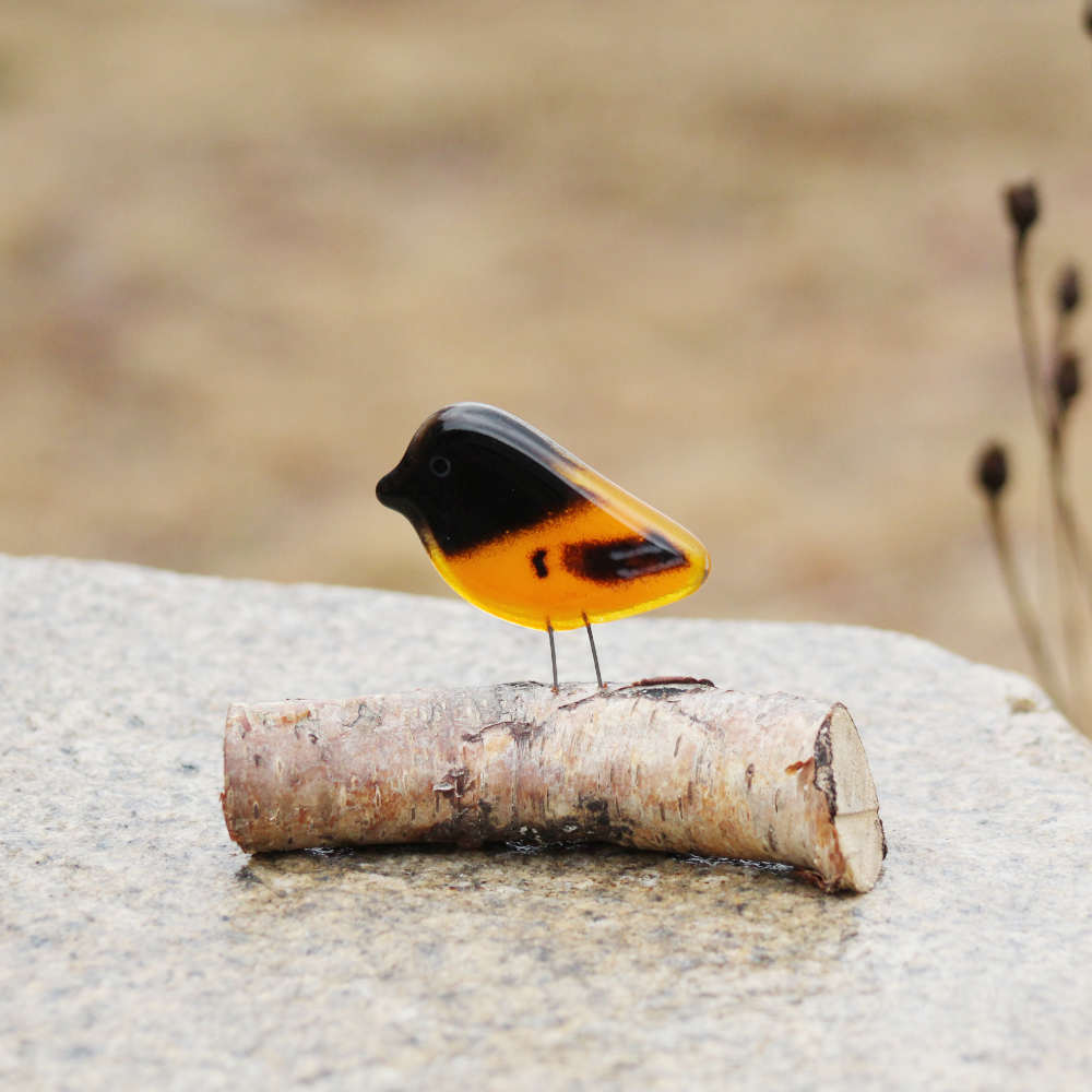 Orange and Black Baltimore Oriole Chick made from glass and perched on a  log