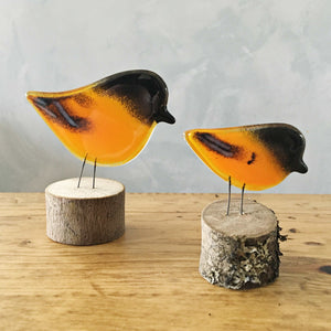 Two orange, black and white glass birds (Baltimore Orioles) on log perches